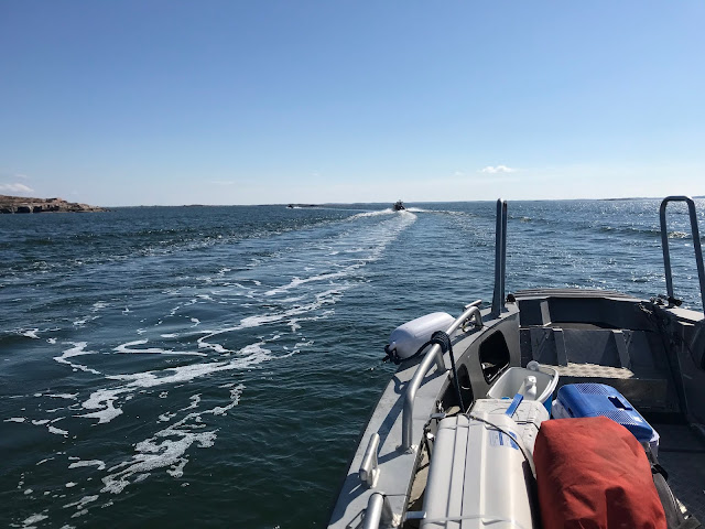 Kolme venettä ajaa peräkanaa merellä
