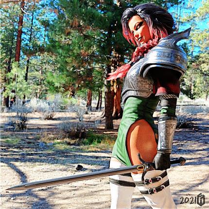 Mit Schwert und Panzerhemd steht Leonie Valorie in einer Waldlichtung und wartet auf etwas.