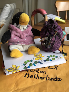 MEme Corina Duyn, small stuffed toy penguin sitting on an envelop, ready to travel abroad