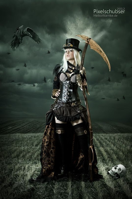 halloween costume idea: A steampunk grim reaper (angel of death) cosplay. A woman wears a bra, corset, skirt, stockings, goggles, top hat and holds a scythe in a field by a skull and raven/crow.