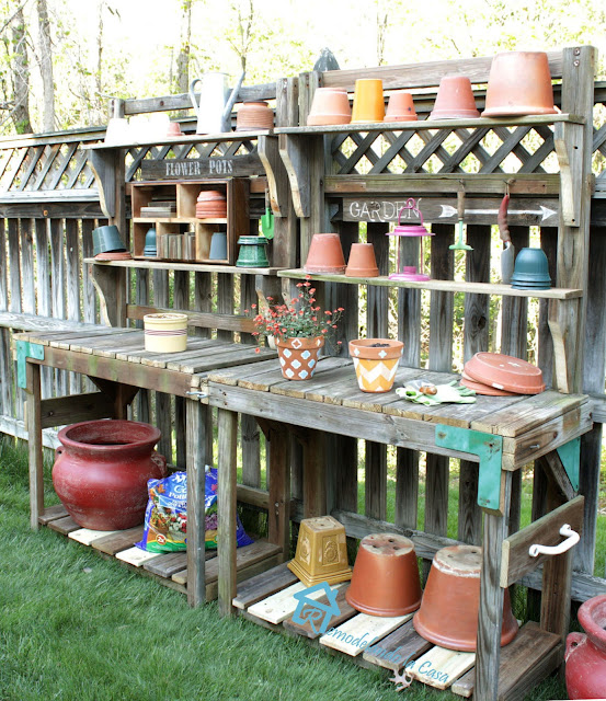 potting bench made out of a playset with lots of planters on it.