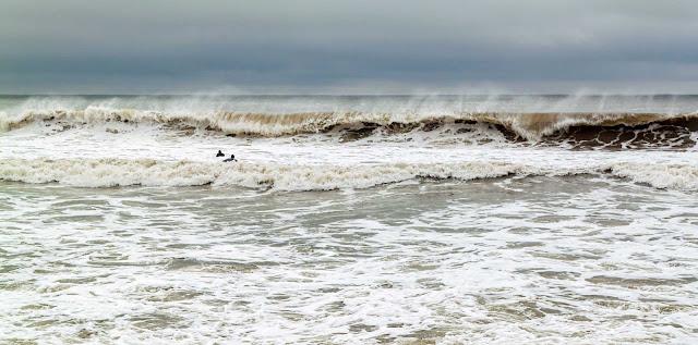 Dos nadadores avanzan sobre las olas del  mar.
