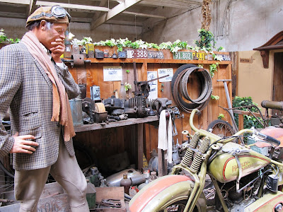 Full-scale model of a 1920s man in a workshop, contemplating a vintage Harley Davidson motorcycle.