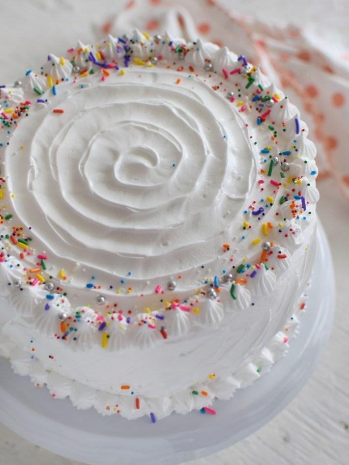 Torta de vainilla decorada con merengue blanco y lluvia de colores para cumpleaños