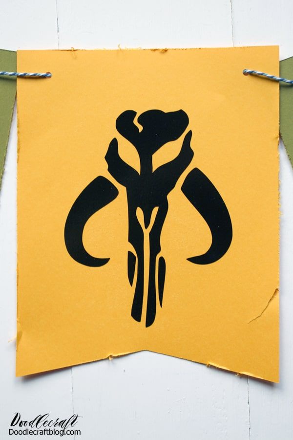 Paper bunting flag with Mandalorian symbol silhouette on it for the perfect diy party decorations.