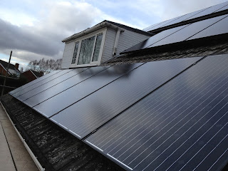 16 All black solar panels mounted in landscape