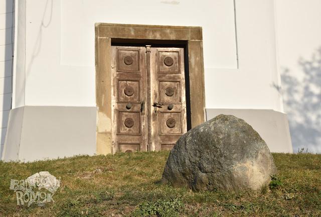 Egy félig földbeásott nagy kő a fehérfalú templom előtt, háttérben a templom ódon faajtaja kőkeretben.