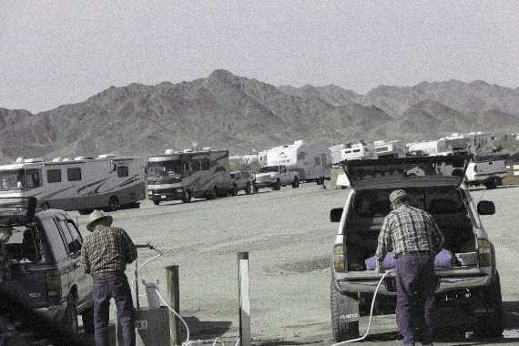 vans and rvs lined up in Quartzsite, AZ, mountains in back. Men in foreground getting water from public spigots.