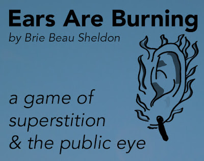 "a dark blue box with the text ""Ears Are Burning by Brie Beau Sheldon, a game of superstition & the public eye"""
