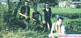 The band pose next to a swamp in Bangkok. Further out towards Bangkok's new airport, these areas still exist and look the same as in this photo by  Pennie Smith
