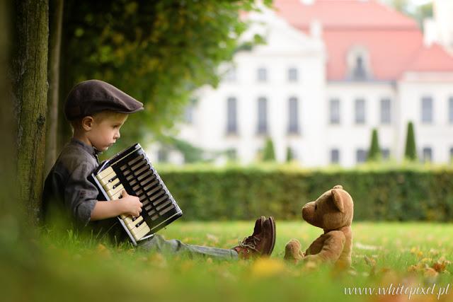 Chłopiec gra akordeonem misiem w parku fotografia stylizowana