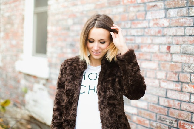 Fur jacket, graphic tee, dark denim and black slip on sneakers
