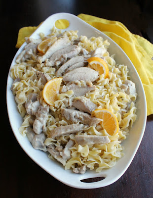 large serving dish filled with pasta, creamy lemon chicken and chicken wedges