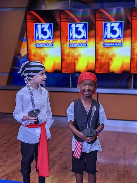 two young boys wearing homemade outfits for Gasparilla. They are on the set of a local tv news station.