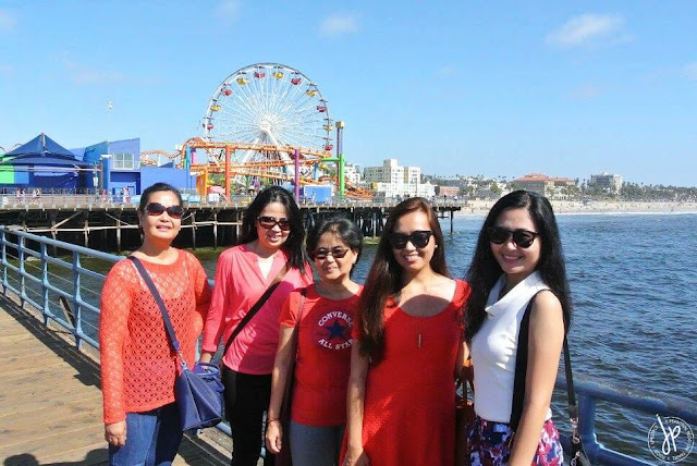 group photos of ladies at pier with ferris wheel