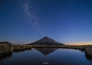 Stars over Mt Taranaki reflect in a still Pouakai Tarn after sunset.