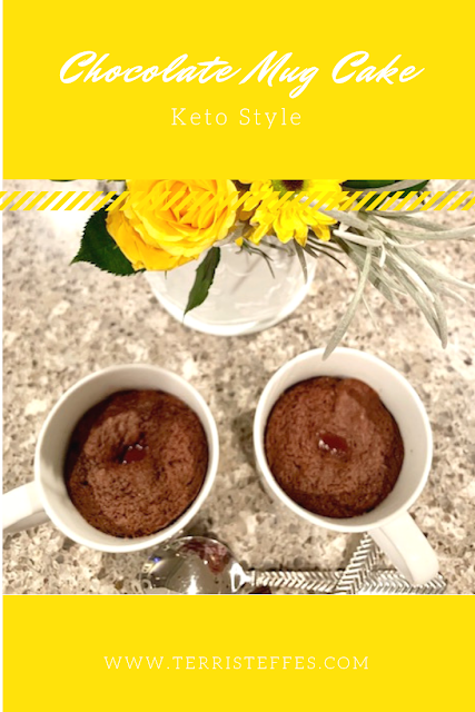Chocolate mug cake with a bouquet of yellow flowers.