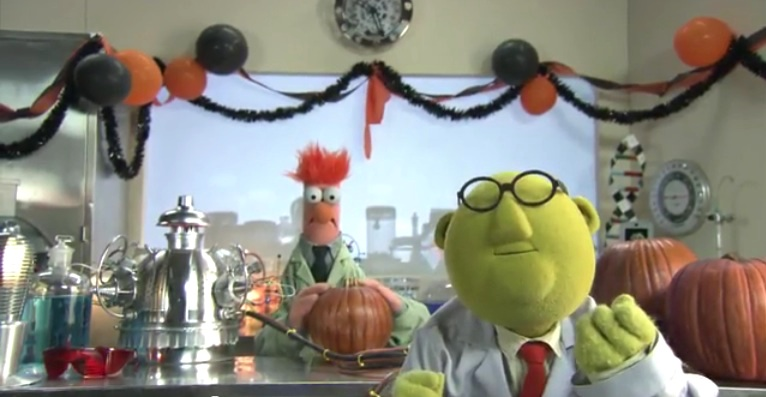 Dr. Bunsen Honeydew and Beaker with several pumpkins in lab adorned for Halloween