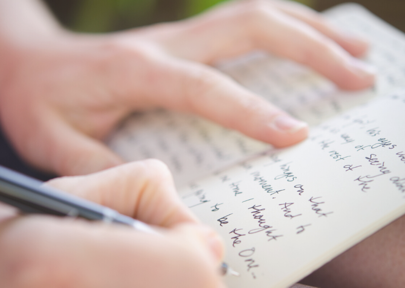 A lady writing in a journal in a post about how to start journaling and make it a habit