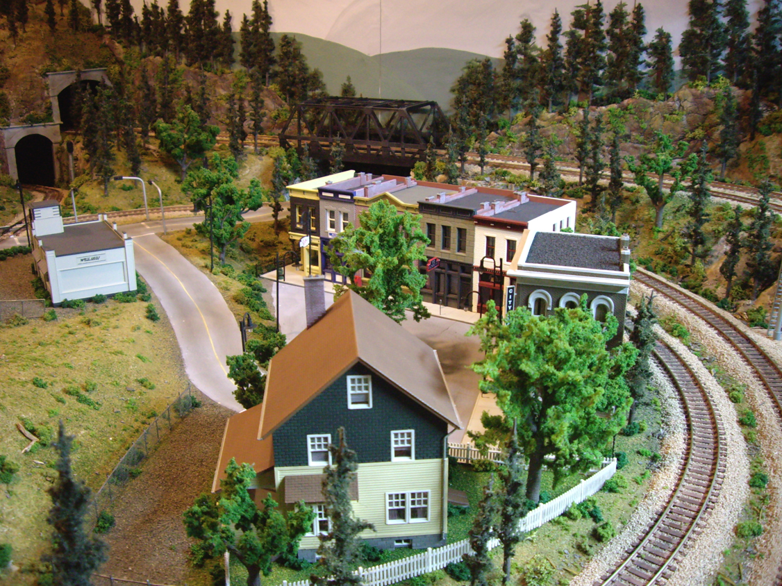A downtown scene complete with scenery and several building kits surrounded by train tracks