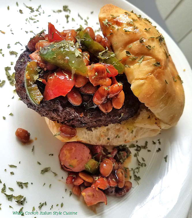 this is how to make a chili with hotdogs in it then added to a grilled hamburger on a ciabatta roll. This is sitting on a white plate with sprinkles of dried parsley and more chili falling off the burger.