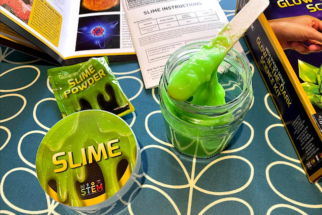 A glass jar with glow in the dark slime made in it next to the box contents