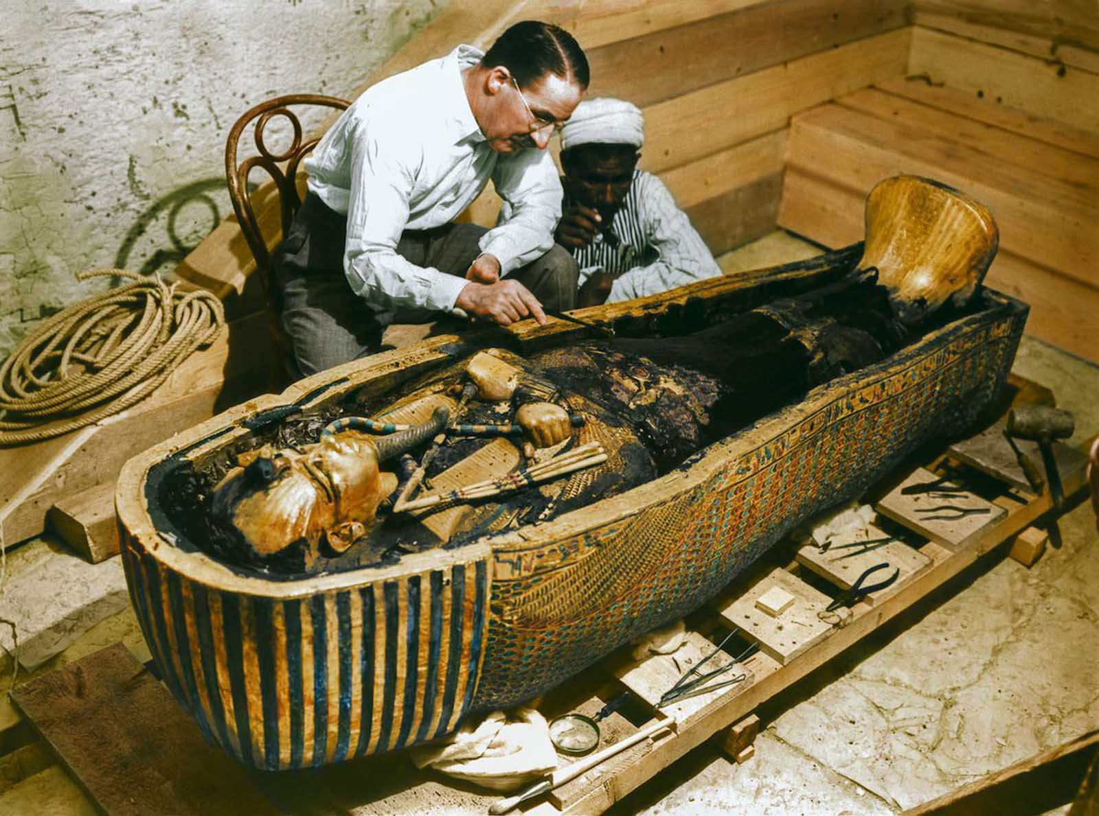 Carter and a worker examine the solid gold innermost sarcophagus.
