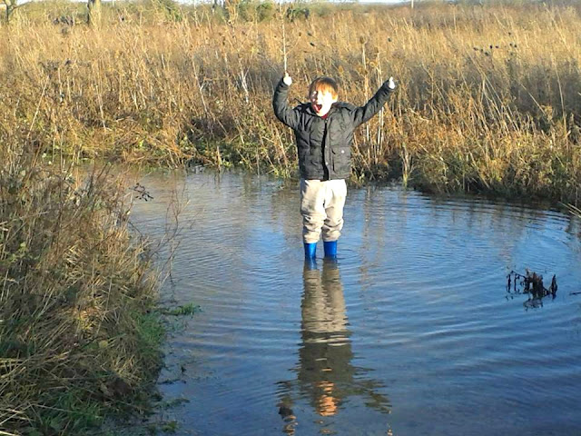 Boy standing in large puddle wearing wellies.