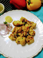 Serving chicken reshmi kabab in a plate with onion sliced and lemon wedges.