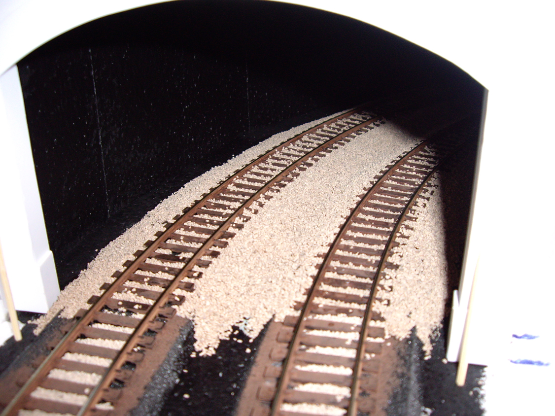 A set of half ballasted model railroad tracks coming out of a styrene tunnel portal