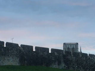 photo of the York skyline at sunset, showing the walls and the Minster tower