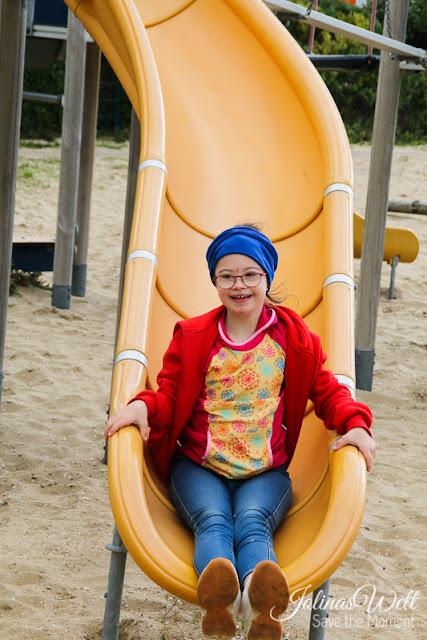 Mädchen mit Down-Syndrom auf Rutsche