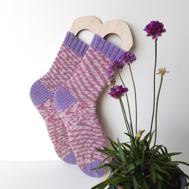 A pair of socks on sock blockers balanced on their toes against a cream background.  The socks have purple cuffs, heels and toes and the body of the socks are pink and white.  In the foreground is a plant with pink flowers.