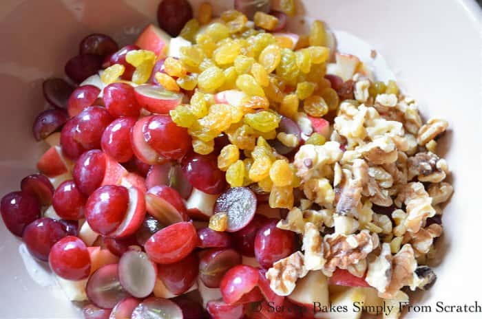 In a bowl grapes, gala apples, red grapes, golden raisins, and walnuts to make Waldorf Salad.