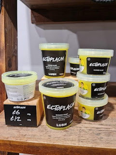 A row of large plastic clear tubs filled with bright neon yellow-green slime with a black label with ectoplasm shower slime lush in white font on a large light brown wooden shelf on a bright background