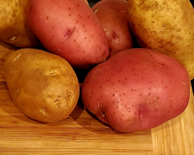 this is a photo of red and white potatoes unpeeled on a wooden board
