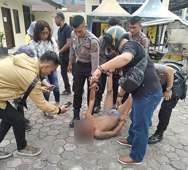 Tersangka pelaku curanmor saat fiamankan polisi dari amuk massa.