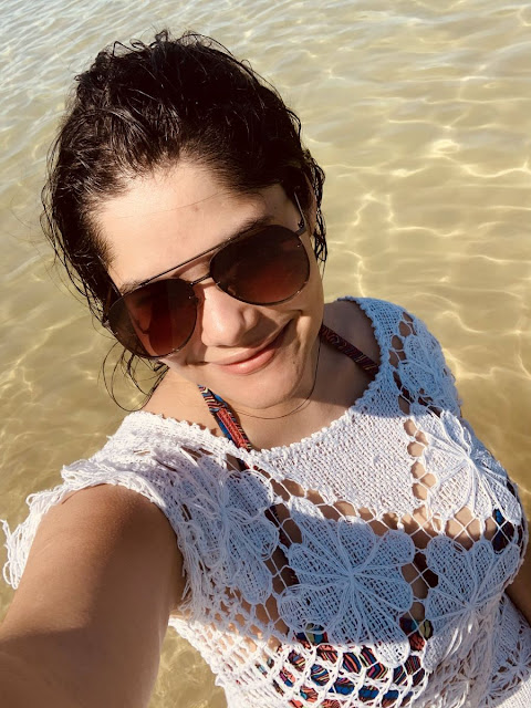 selfie de mulher de oculos escuro, saida de banho de trico branco na praia