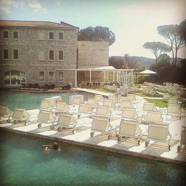 Rows of deckchairs and a man swimming in the Saturnia hotel pool