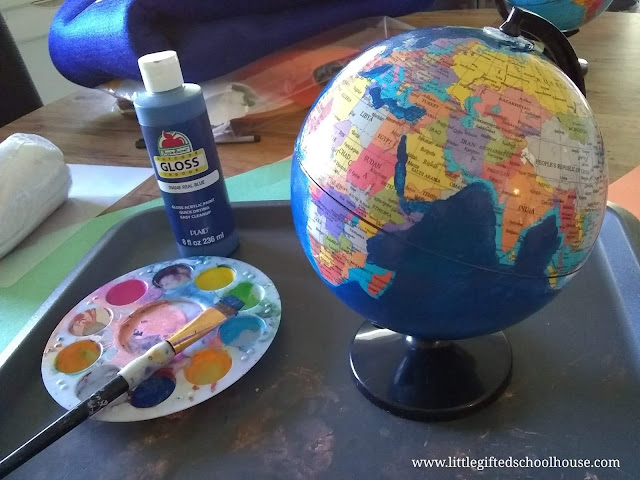 DIY Montessori Sandpaper Globe with the water portions of the globe partially painted blue