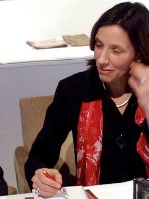 Hochgradig amüsierte Dolmetscherin mit rot-weißem Schal und rotem Füller