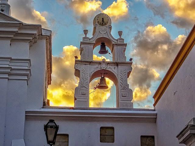 El cielo nuboso brilla detrás del campanario de la Iglesia del Pilar
