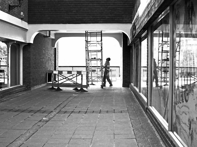 Man moving a small scaffold tower while working on repairs in shopping centre. Black and white with reflections in windows.