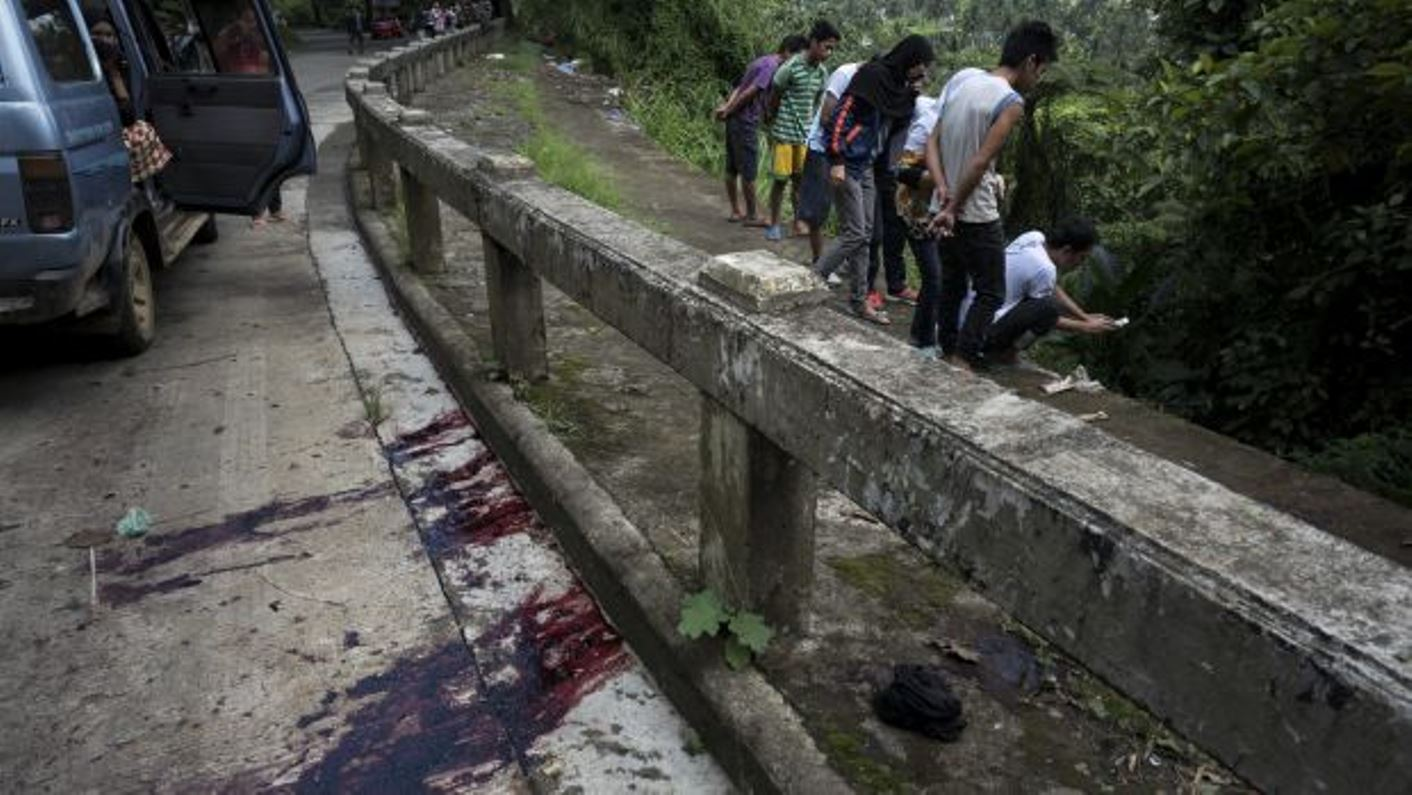 Blood stains the roadside as civilians view unidentified bodies believed to have been executed and dumped in a ditch by militants