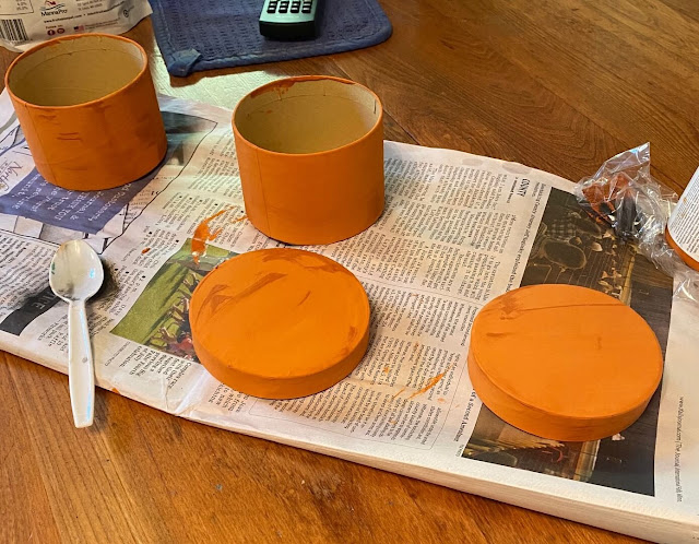 Photo of two Dollar Tree round boxes being painted orange