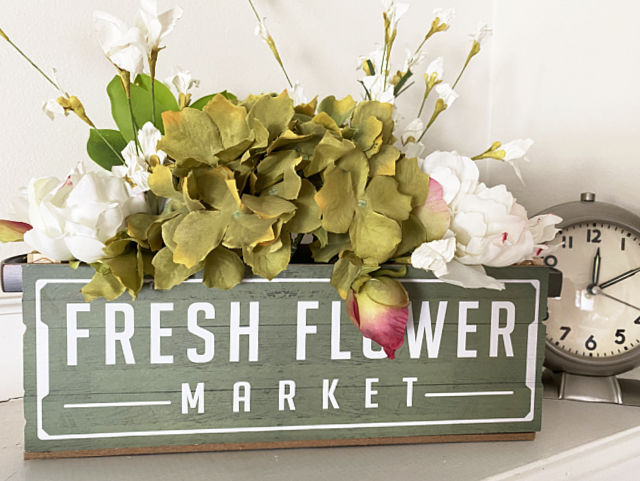 dollar store sign crate filled with flowers