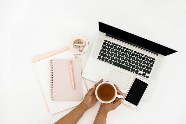 Flatlay mãos femininas segurando uma xícara em frente ao computador / ambiente de estudos