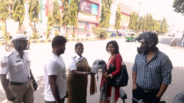 Lady traffic police giving away the helmet
