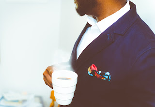 A man in navy blue suit, coffee cup in his hand.