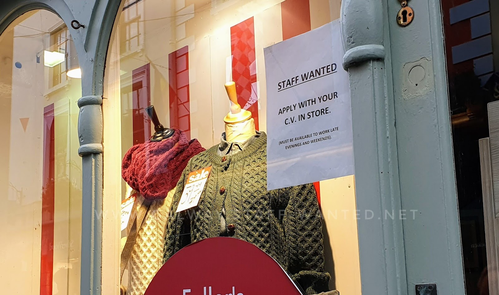 Shop window with job advertisement sign, and aran-knitwear sweaters in traditional cream, also green and red.